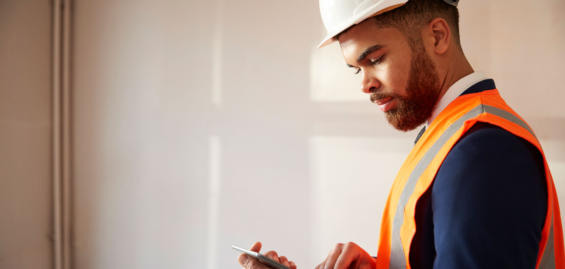 Man in bright orange jacket and hardhat looking at tablet