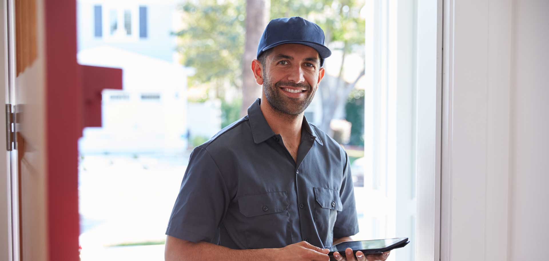 Man smiling with tablet in hand, blue cap on