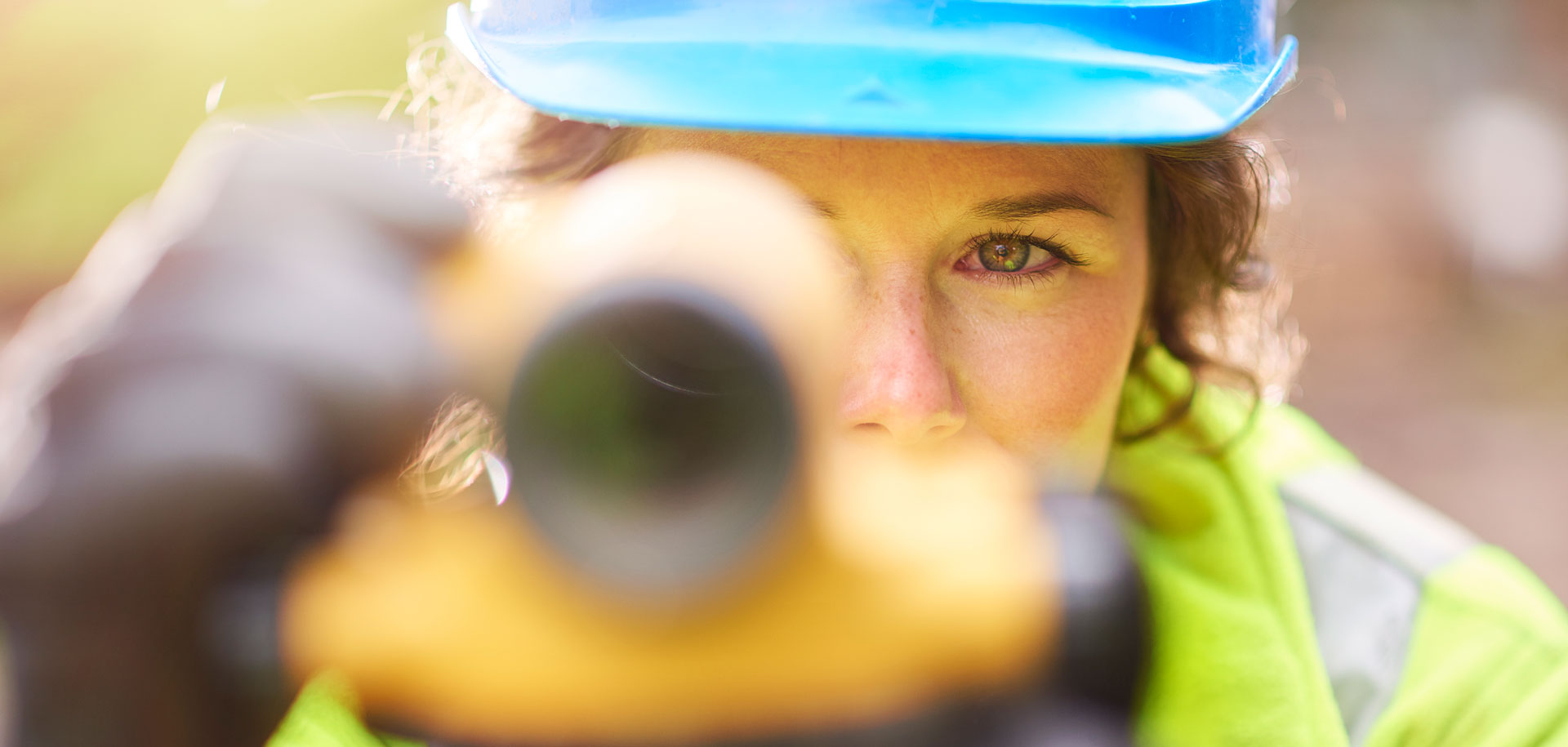 Woman looking through lens, surveying