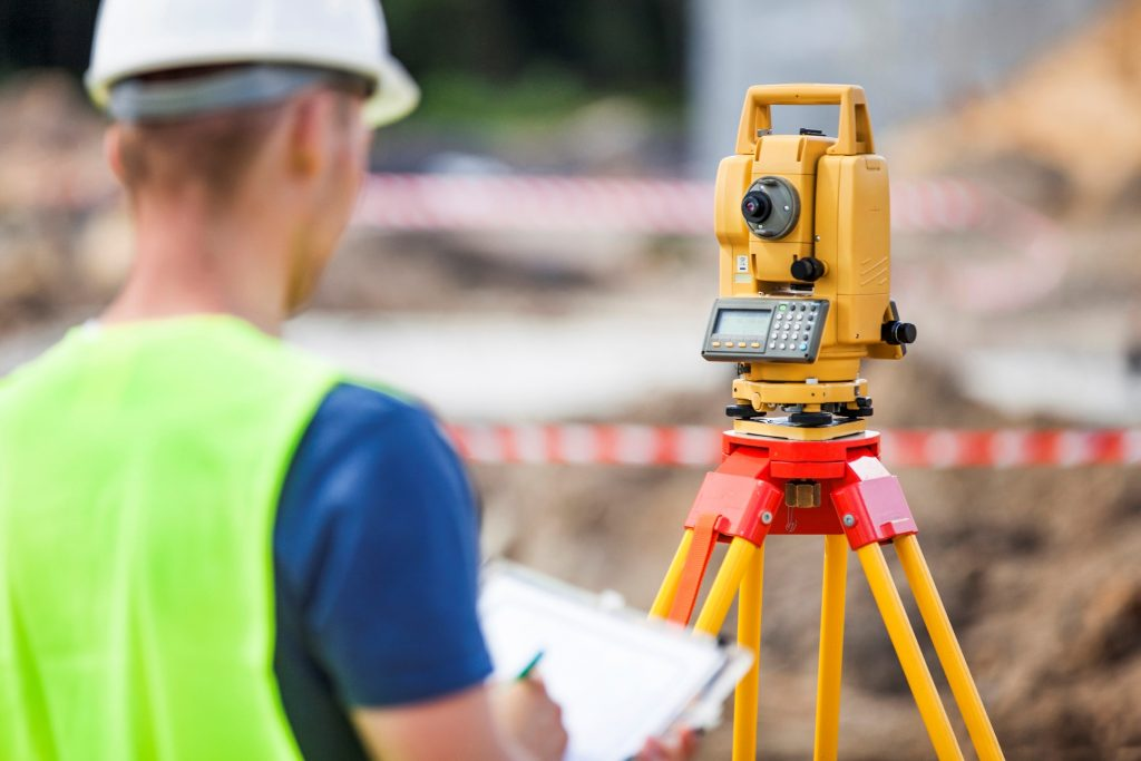 Man looking at surveying device with tablet