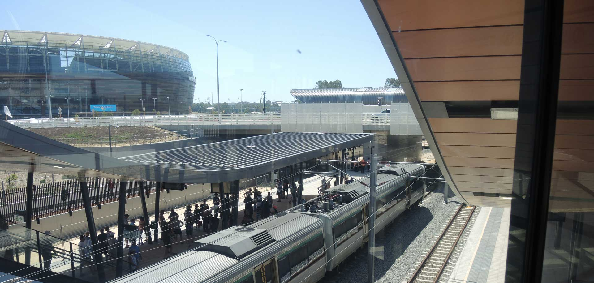 Train travelling along line with stadium in background