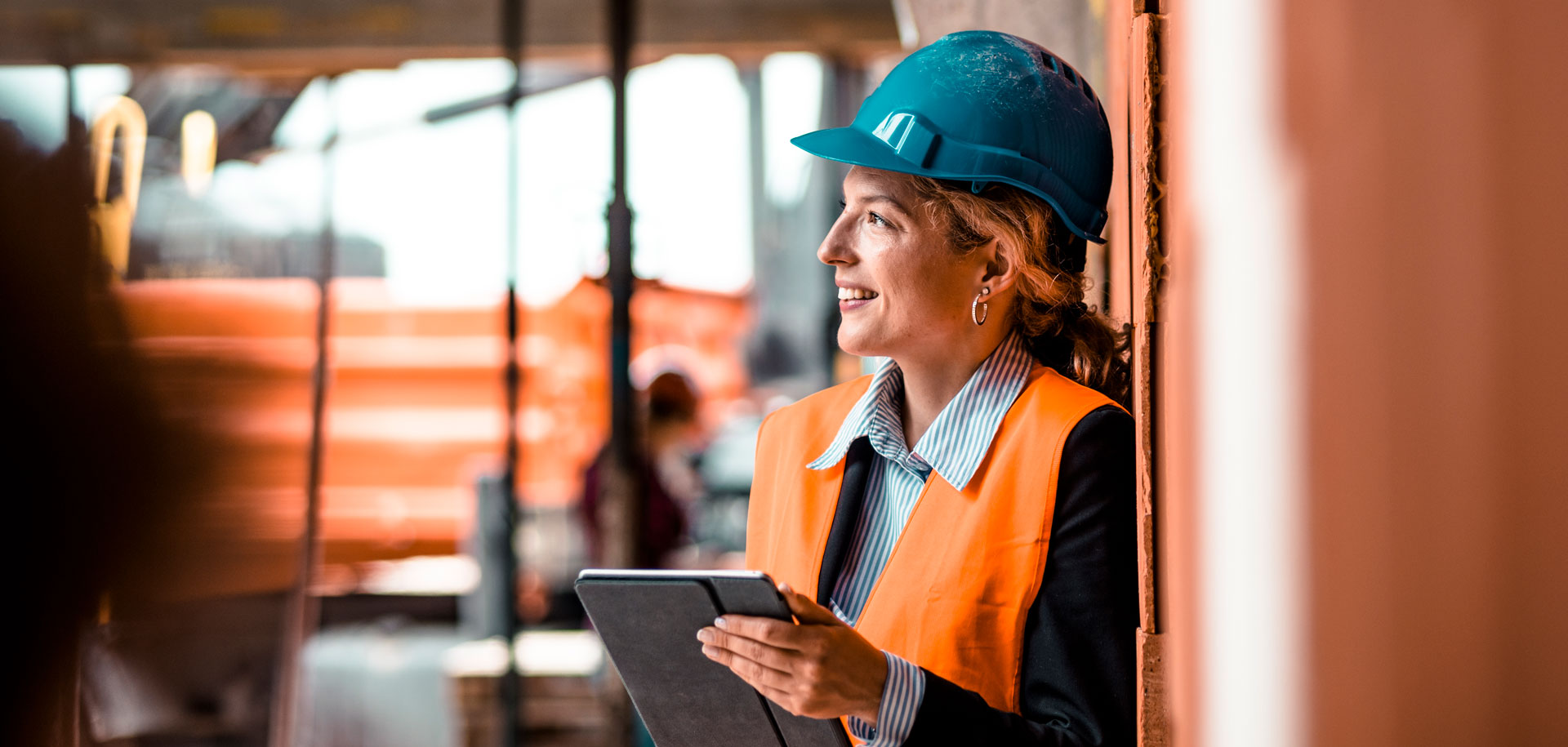 Woman smiling with hardhat on and clipboard in hand