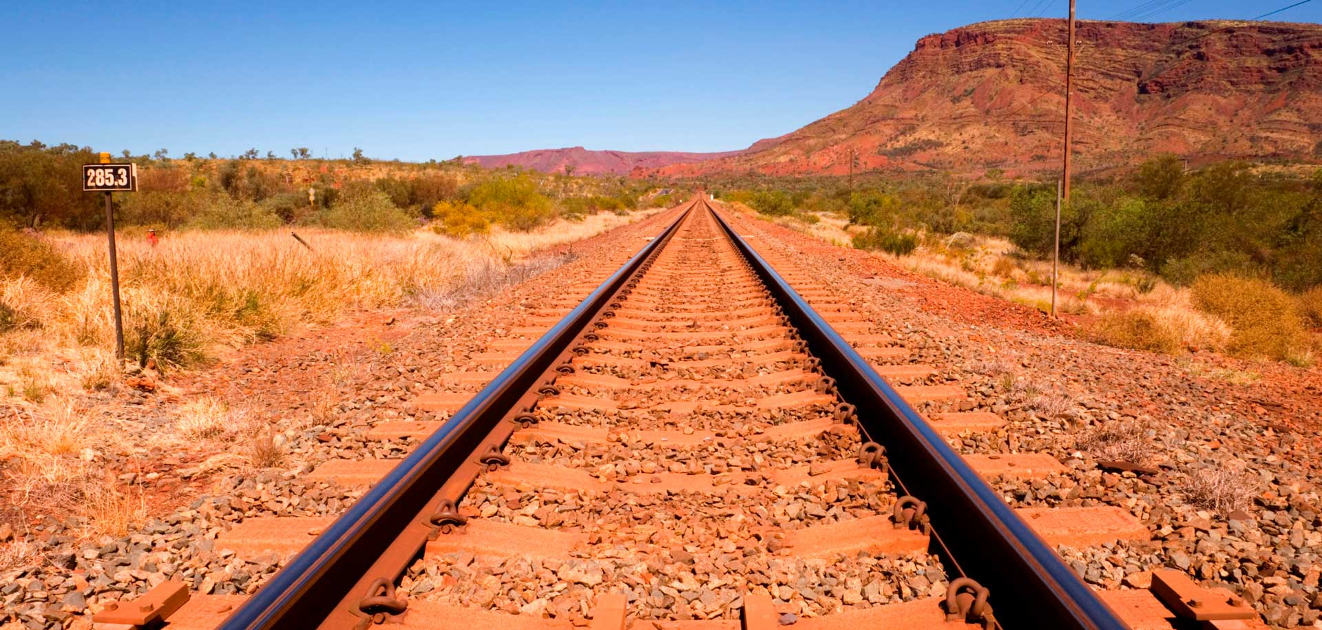 Railway tracks with red sand in background