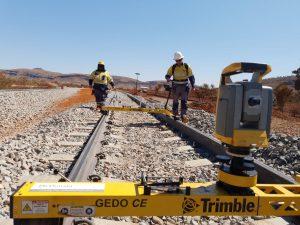 two men walking by surveying equipment trimble