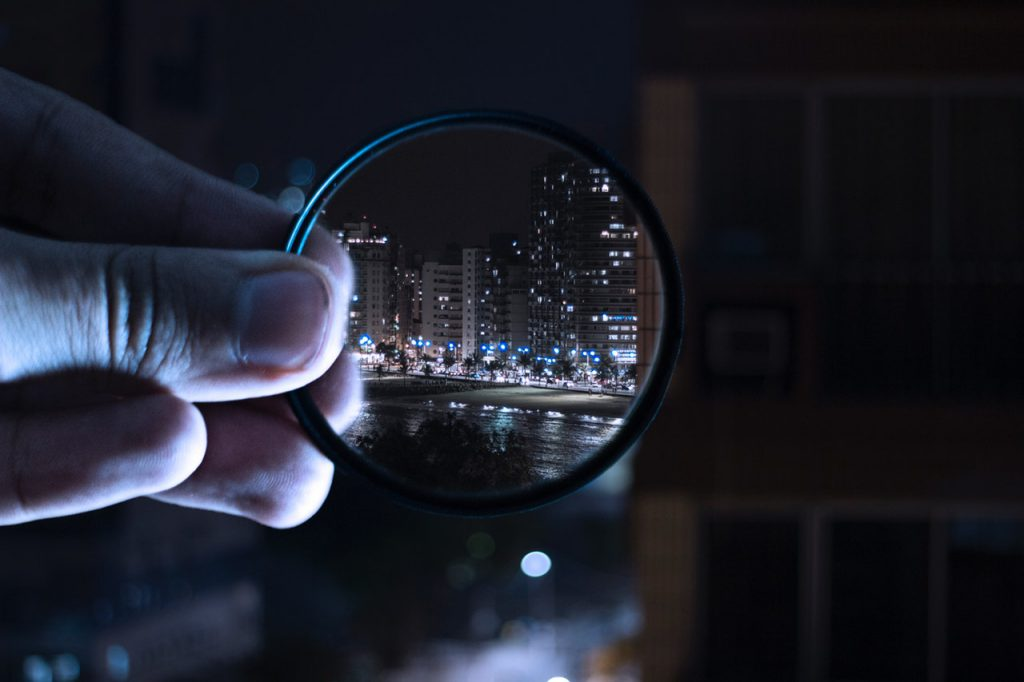 person holding magnifying glass looking at city